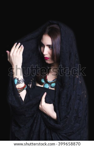 Pretty caucasian woman in abaya on black background - stock photo