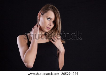 Pretty Caucasian woman looking thoughtfully at the camera, her hands on her neck - stock photo