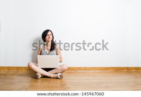 Pretty caucasian woman with a laptop sit on the floor