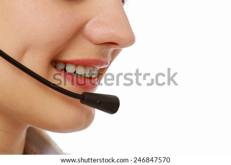 Pretty caucasian woman with headset smiling during a telephone conversation. Part of face isolated on white background - stock photo