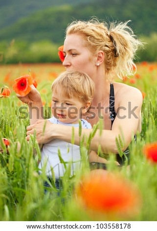 Pretty caucasian woman with her child in poppy field, focus on mother