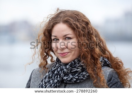 Pretty Caucasian woman with long curly hair on wind, head and shoulders portrait  - stock photo