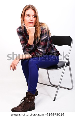 pretty charming girl Caucasian blonde in a plaid shirt and blue pants sitting on a chair, thoughtfully, looking at the ceiling, thinking, thinks, question,  isolated on white - stock photo