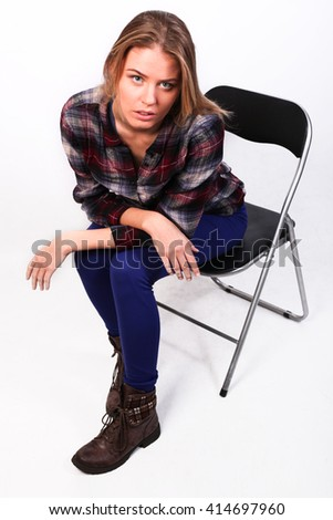 pretty charming girl Caucasian blonde in a plaid shirt and blue pants sitting on a chair, bent body and looking at the camera, isolated on white - stock photo