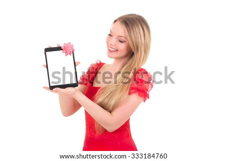 Pretty cheerful girl in a santa hat on new year holding tablet computer touch pad gadget with white screen and bow - stock photo