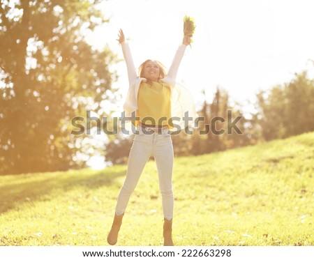 Pretty cheerful woman having fun in sunny autumn day - stock photo