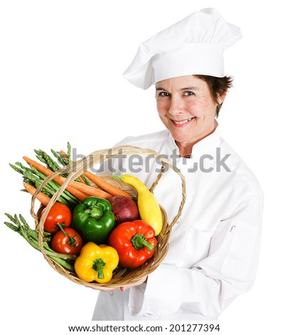 Pretty chef holding a basket of fresh vegetables.  Isolated on white.   - stock photo