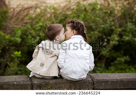 pretty child fell lovely and happy it`s  first kiss - stock photo