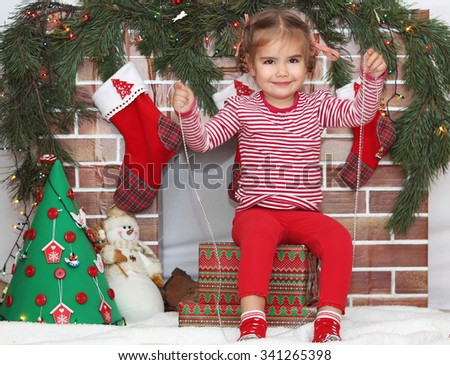 Pretty child girl sitting on packed gifts and holding a garland decoration near Christmas decorated fireplace, winter holiday family concept - stock photo