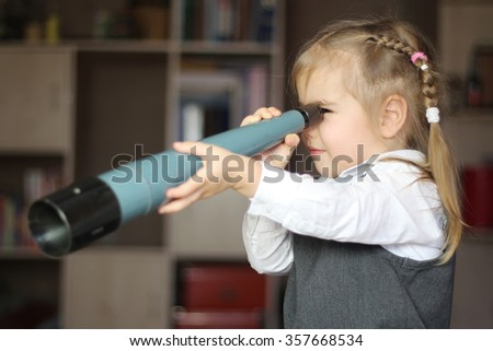 Pretty child girl wearing in grey dress and white shirt looks forward through spyglass, education concept, indoor - stock photo
