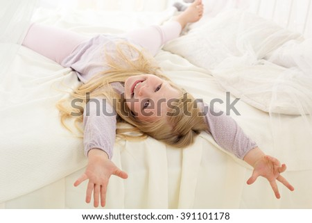 Pretty child is lying down on bed with white sheets - stock photo