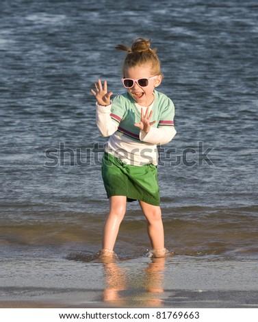Pretty child on the beach posing in the sea - stock photo
