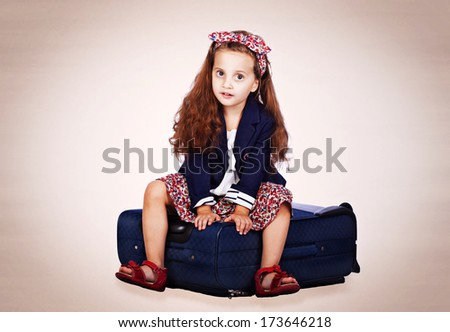 pretty child on the suitcase - stock photo