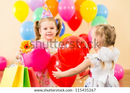 pretty children with colorful balloons and gifts on birthday party