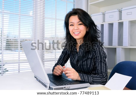Pretty Chinese Business Woman With long Hair Sat At Her Office Desk - stock photo