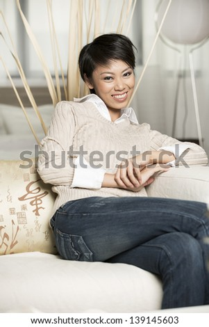 Pretty Chinese woman relaxing at home on the sofa.