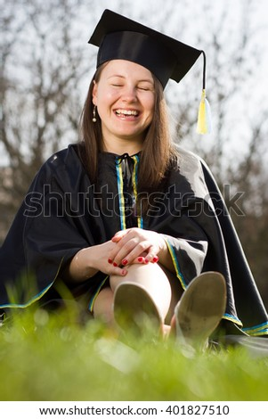 Pretty clever college / university student / girl after graduation day / completion ceremony wearing gown and mortarboard and enjoying completion during lovely sunny day (color toned image) - stock photo