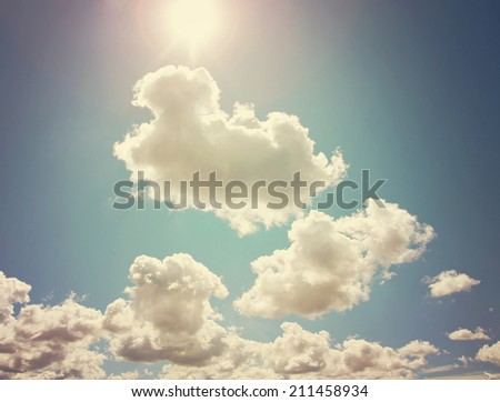 pretty clouds and a sun flare on a sunny day with blue sky toned with a retro vintage instagram filter  - stock photo