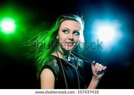 Pretty clubber dancing and looking sideways with smile. Closeup. - stock photo