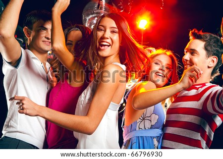 Pretty clubber dancing surrounded by her friends and looking at camera with smile - stock photo