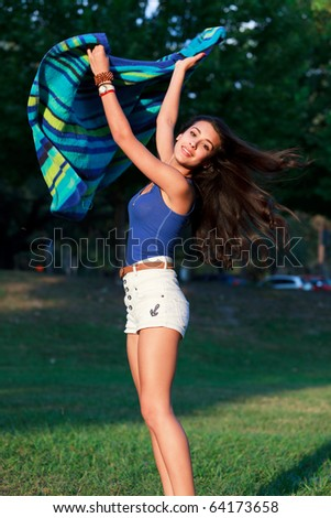 Pretty College Teenager waving a beach towel on the lawn of a university campus.