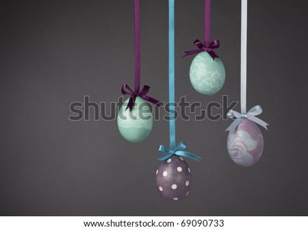 Pretty Colored Easter Eggs hanging on Ribbons with bows on a grey background. - stock photo