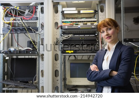 Pretty computer technician smiling at camera beside server in large data center