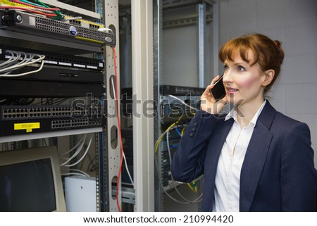 Pretty computer technician talking on phone beside open server in large data center - stock photo