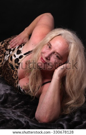 Pretty, confident, middle aged woman in her fifties smiling on a dark background - stock photo