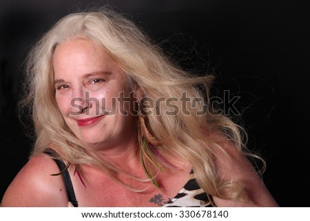 Pretty, confident, middle aged woman in her fifties smiling on a dark background