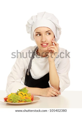Pretty cook chief sitting on the table with salad