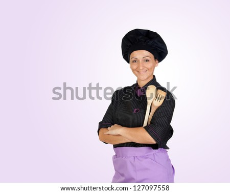 Pretty cook girl with wooden cookware isolated on purple background