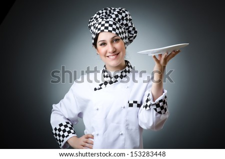 Pretty cook with kitchen utensils - stock photo