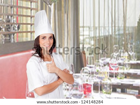 Pretty cook woman saying Ok in her restaurant - stock photo
