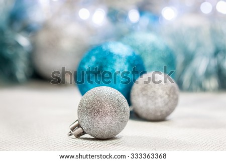 Pretty cool toned Christmas decoration background with blue, white and silver textured glitter baubles entwined in tinsel in a full frame view - stock photo