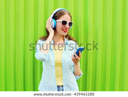 Pretty cool woman listens to music in headphones using smartphone over green background - stock photo