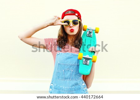 Pretty cool woman with skateboard having fun over white background - stock photo