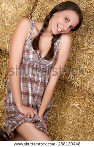Pretty country girl in hay - stock photo