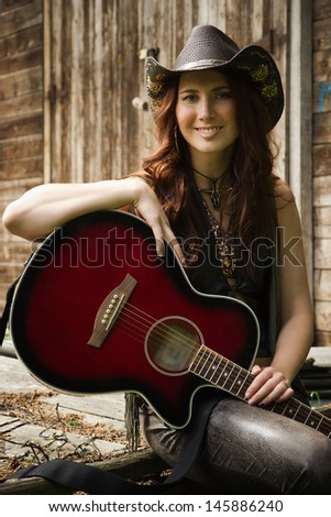 Pretty country girl with guitar on the ranch - stock photo