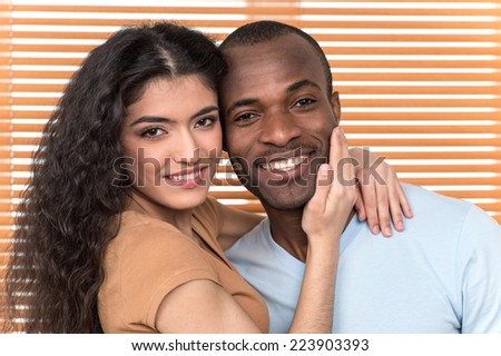 pretty couple hugging and looking into camera. African man and Hispanic woman standing close before shutters
