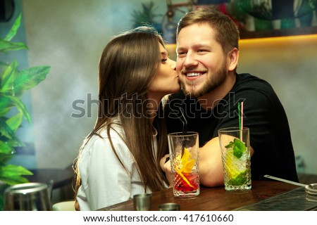 Pretty couple in love having fun in the bar with alcohol cocktails. Girl kisses her boyfriend. Guy smiling and looking away. - stock photo