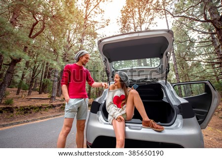 Pretty couple in sweaters and hats sitting in the car trunk on the forest roadside. Young family traveling by car in the pine forest - stock photo
