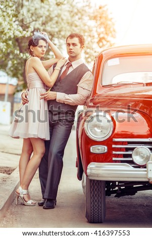 Pretty couple is going to make a journey on their red car.