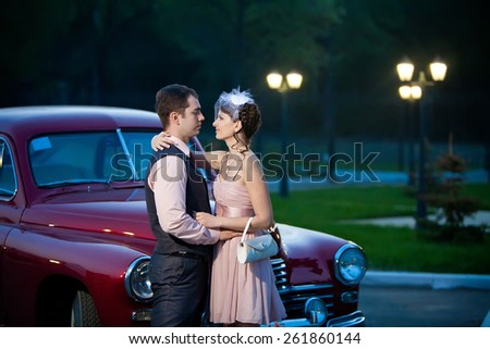 Pretty couple near the vintage car on the night city background - stock photo