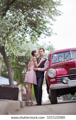 Pretty couple near the vintage car on the sunset background - stock photo