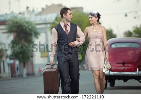 Pretty couple with the trunk on the vintage car background - stock photo