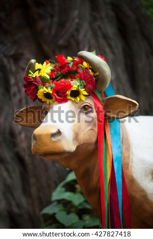 Pretty cow in Ukrainian bright wreath with flowers and ribbons