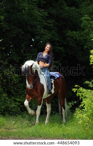Pretty cowgirl bareback riding painted horse