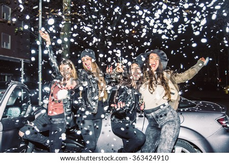 Pretty crazy girls dancing, throwing confetti and drinking wine - Young women partying outdoors before to go in a club - stock photo