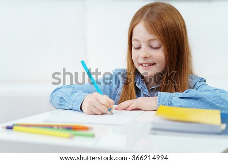 Pretty creative little girl drawing with a colored pencil as she does her schoolwork at home smiling with pleasure as she amuses herself - stock photo